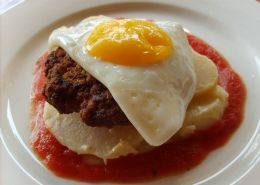 Beefy breakfast-Homemade beef patty with a fried egg on sliced potatoe baked in cream and homemade tomatoe sauce.