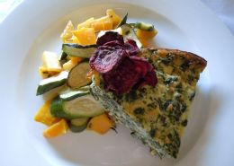 Spinach mozzarella tart-Ano crust tart served with roasted butternut and baby marrow and garnished with beetroot.Vegetables can be changed for salad. This is a gluten free meal.