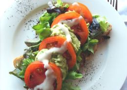 Avo Tomatoe Sandwich-Pressed avo with tomato on homemade brown bread and topped with a homemade creamy dressing.