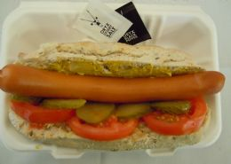 Bockwurst on a gluten free roll with German mustard, gherkin and tomato